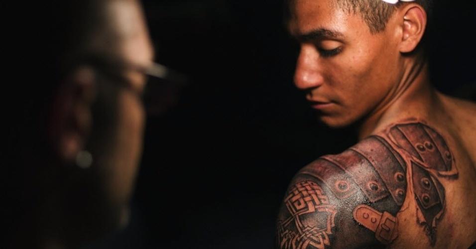18.mai.2013 - Tatuador trabalha no desenho de um crânio e uma armadura romana no braço de participante de encontro sobre tatuagens em Nova York