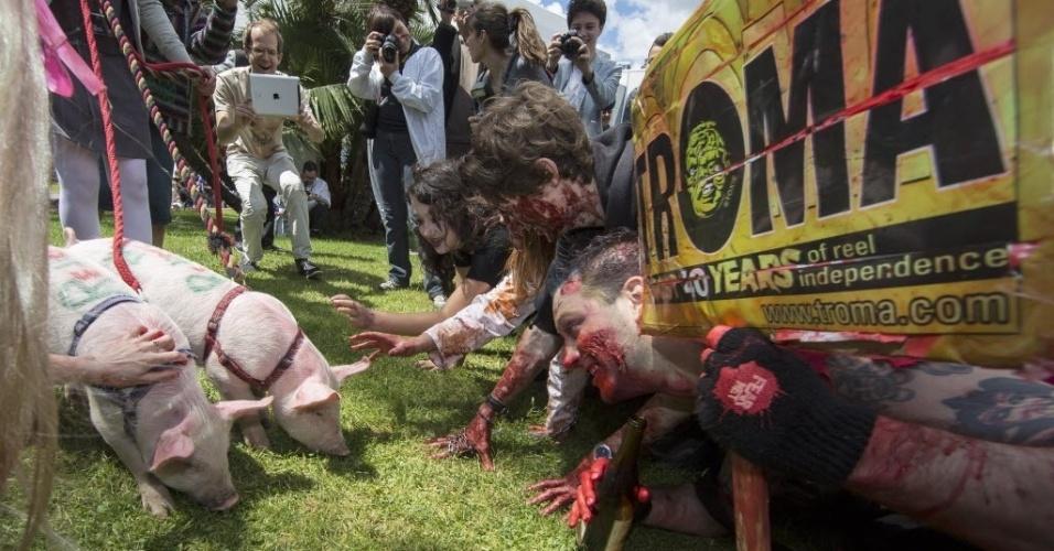 19.mai.2013 - Membros da Troma, uma produtora de filmes independentes, se vestem de zumbis e brincam com porquinhos durante um flashmob em frente ao Palais des Festivals em Cannes