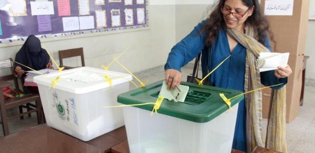 Mulher deposita seu voto em urna durante dia de eleição em Karachi, em 2013 - EFE
