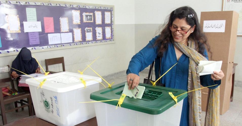 19.mai.2013 - Mulher deposita seu voto em urna durante dia de eleição em Karachi, maior cidade do Paquistão