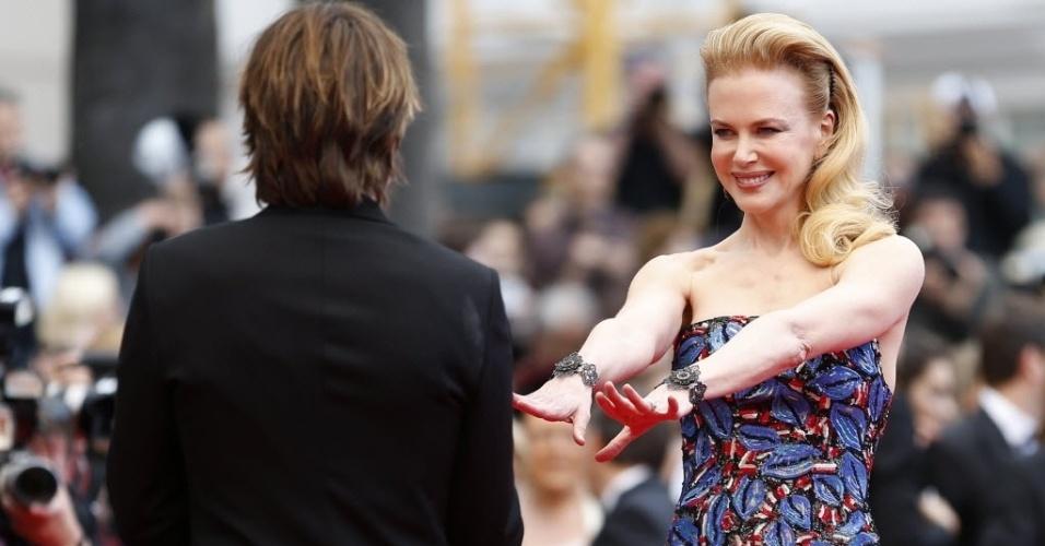 19.mai.2013 -  Nicole Kidman estica os braços em direção ao marido, o cantor Keith Urban, no tapete vermelho,  antes da exibição do filme