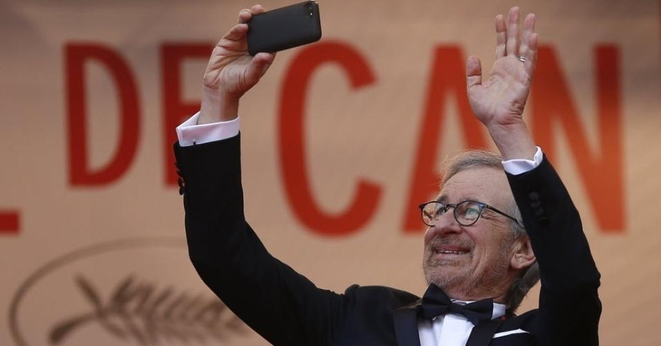 19.mai.2013 - O diretor e jurado do festival, Steven Spielberg, tira fotos com o celular no tapete vermelho antes da exibição do filme