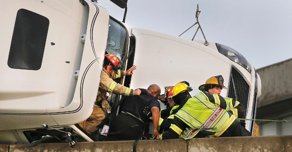 19.mai.2013 - Bombeiros da cidade de Shawnee, em Oklahoma, resgatam o motorista Marco Corr, cujo caminhão tombou pela passagem de um tornado neste domingo. Uma pessoa morreu em consequência da forte tempestade que provocou uma série de tornados nos Estados do Kansas, Oklahoma e Iowa, no meio oeste dos Estados Unidos
