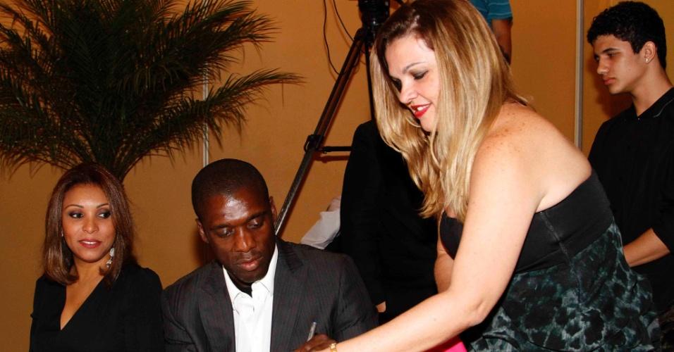 20.mai.2013 - Ao lado da esposa brasileira Luviana, o holandês Clarence Seedorf dá autógrafo a uma fã na festa de premiação do Campeonato Carioca