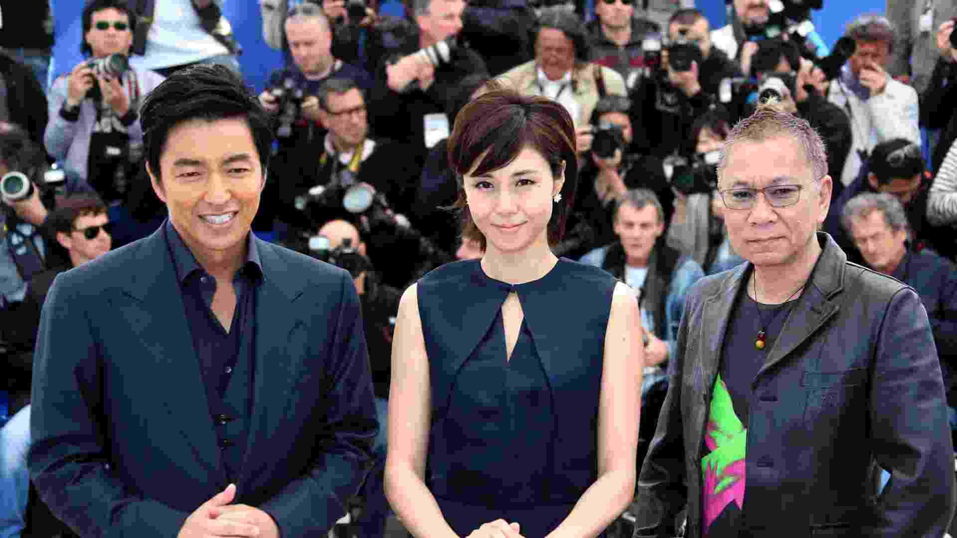 """20.mai.2013 - Os atores japoneses Takao Osawa e Nanako Matsushima e o diretor Takashi Miike posam para a divulgação do filme """"Wara No Tate"""" (Shield of Straw)  no Festival de Cannes - Loic Venance/AFP"""