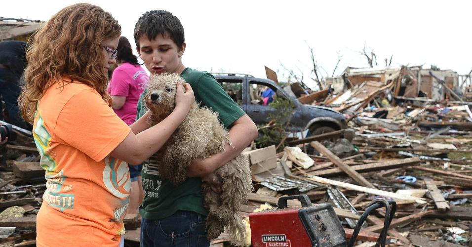 21.mai.2013 - Abby Madi (à esq.) e Peterson Zatterlee acariciam o cão do rapaz, Rippy, encontrado nos escombros de casas do bairro de Moore, em Oklahoma, destruídas pela passagem de um tornado no domingo (19). Ao menos 91 pessoas, 20 delas crianças, morreram em consequência da passagem de tornados pelo centro-sul dos Estados Unidos desde então