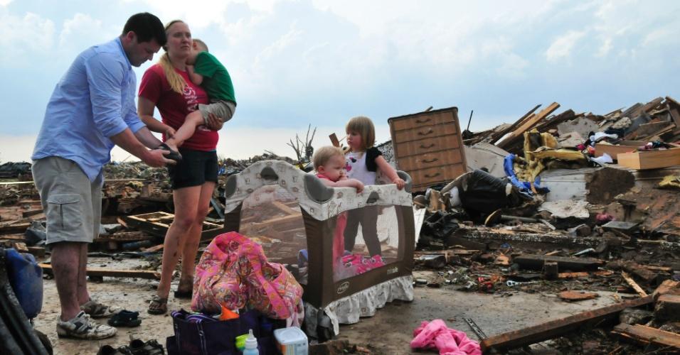 21.mai.2013 - Família caminha entre os destroços de sua casa para tentar recuperar pertences em Moore, nos Estados Unidos, um dia após a passagem de um tornado que deixou dezenas de mortos na região