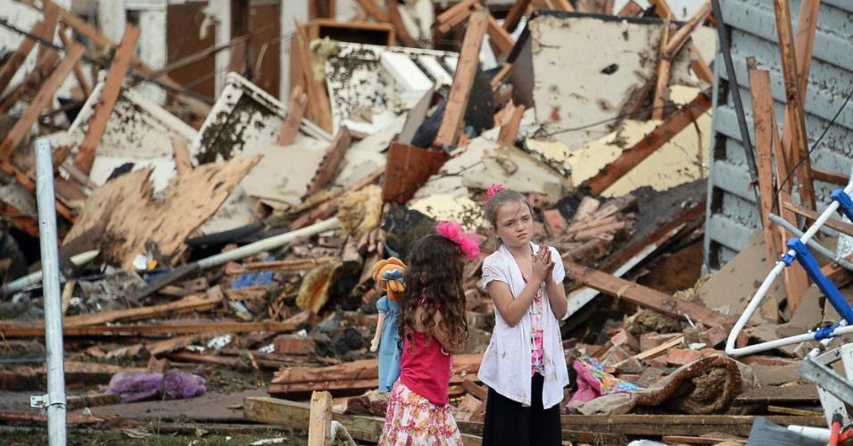 21.mai.2013 - Garotinhas brincam no meio dos escombros de casas destruídas no bairro de Moore, em Oklahoma, atingido por um tornado no domingo (19), que destruiu casas, edifícios e veículos por onde passou. Ao menos 91 pessoas, 20 delas crianças, morreram em consequência da passagem de tornados pelo centro-sul dos Estados Unidos desde então