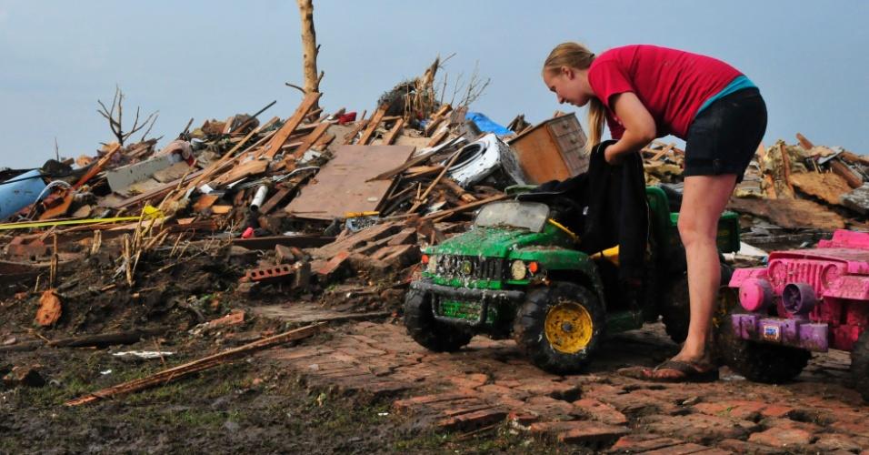 21.mai.2013 - Mulher recupera carrinhos de brinquedo em meio aos escombros de sua casa em Moore, nos Estados Unidos. O desastre natural causou destruição e dezenas de mortes na região