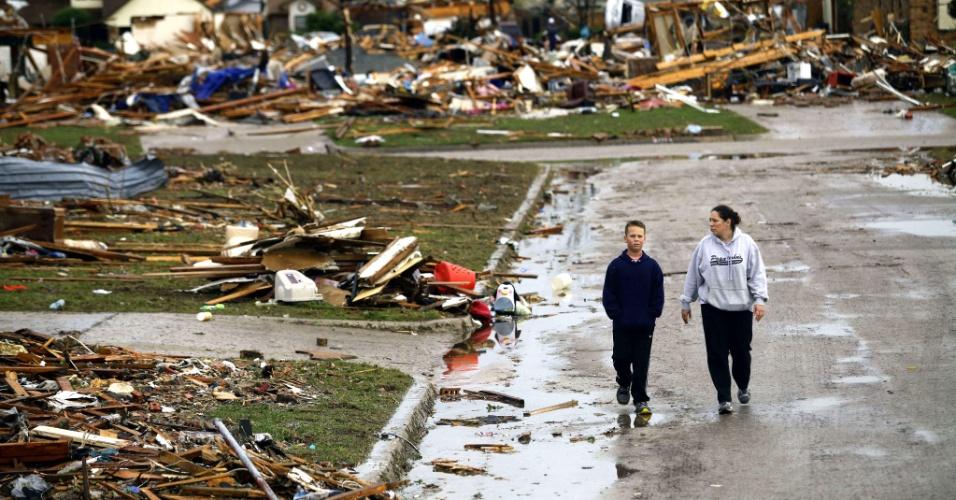 21.mai.2013 - Mulher a garoto caminham, nesta terça-feira (21), por rua onde todas as casas fora destruídas na passagem do tornado de força 5 pela cidade de Moore, no subúrbio de Oklahoma City