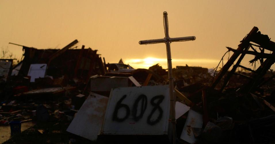 23.mai.2013 - Cruz é colocada em casa destruída após o tornado que atingiu a cidade de Moore, no Estado de Oklahoma, nos Estados Unidos, há três dias. Pelos dados oficiais, foram 24 pessoas mortas, incluindo dez crianças, e 324 feridos