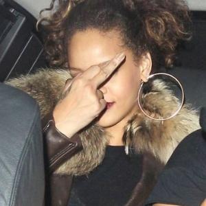 12.out.2011 - Rihanna recebe uma multa de trânsito por estacionar em local proibido em Londres, na Inglaterra, se irrita com a situação e mostra o dedo do meio para os fotógrafos que a aguardavam na frente da boate de striptease