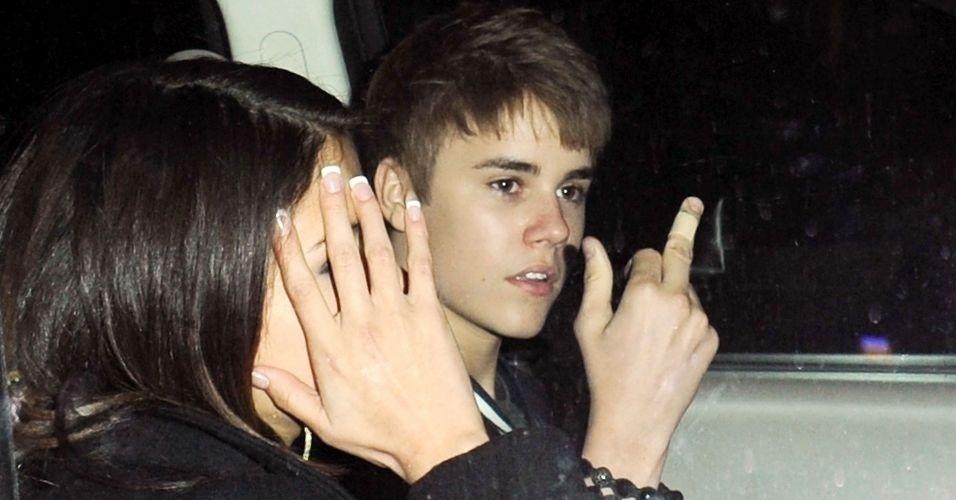 1.mar.2011 - Justin Bieber se irrita ao sair de sua festa de aniversário de 17 anos em um restaurante de Los Angeles, e ao lado de Selena Gomez, o cantor mostrou o dedo médio para os fotógrafos. Dois dias depois, o ídolo adolescente pediu desculpas pela atitude