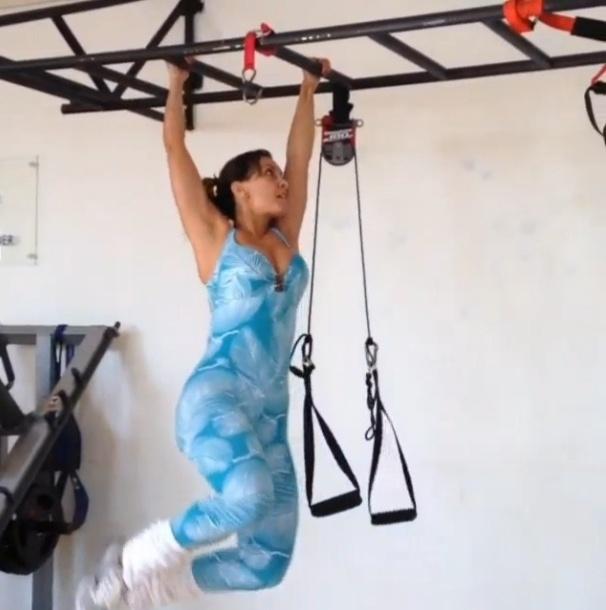 5.jul.2013 - A ex-BBB Lia Khey sua a camisa numa aula de circuito intenso. Na imagem, ela faz exercícios em suspensão