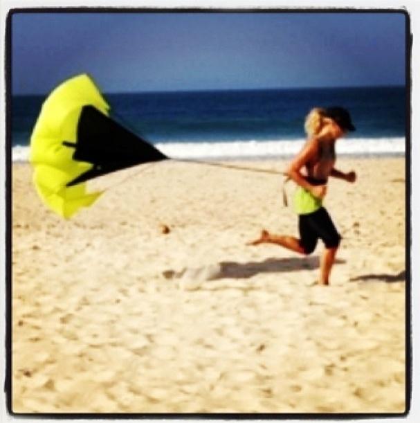 22.jul.2013 - A atriz Carolina Dieckmann corre com um paraquedas na praia para manter a forma