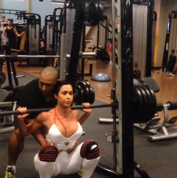 13.nov.2013 - Para fazer o agachamento da forma correta, Gracyanne Barbosa conta com a ajuda do personal trainer. Ela faz quatro séries de 10 repetições deste exercício