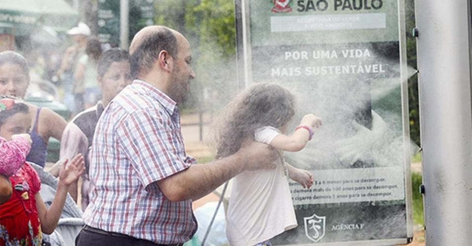 19.jan.2015 - Adulto ajuda criança a se refrescar no parque Ibirapuera; calor bateu recorde na capital paulista