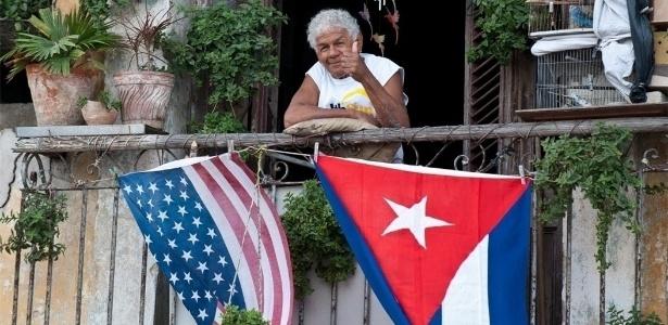 16.jan.2015 - Cubano acena de varanda decorada com bandeiras dos EUA e de Cuba, em Havana