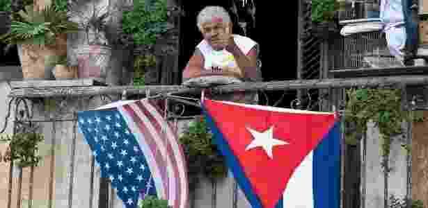 16.jan.2015 - Cubano acena de varanda decorada com bandeiras dos EUA e de Cuba, em Havana - Yamil Lage/ AFP