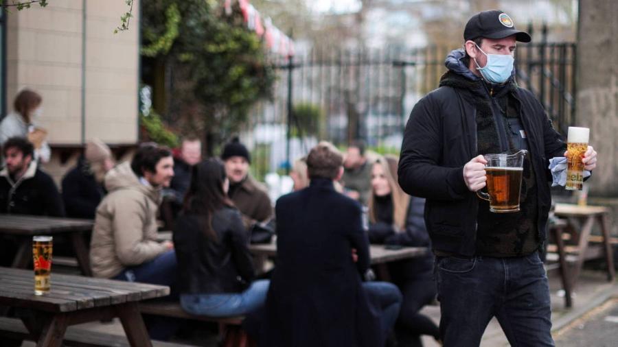Homem carrega copos com cerveja em pub em Londres, na Inglaterra - Hannah Mckay/Reuters