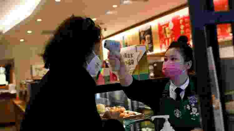 Funcionária mede temperatura de cliente em unidade da Starbucks em Beijing, na China - Carlos Garcia Rawlins/Reuters