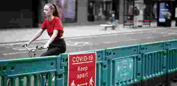 Mulher anda de bicicleta usando máscara de proteção contra o coronavírus no Reino Unido - TOLGA AKMEN / AFP