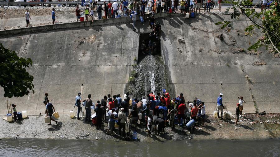 A Venezuela enfrenta uma profunda crise econômica e social; em episódio recente, queda de energia elétrica no país levou a população a coletar água do esgoto - Cristian HERNANDEZ / AFP