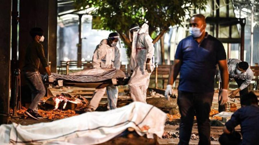 Familiares e funcionários de crematório em Nova Déli, na Índia, carregam corpo de vítima da Covid-19 - Sajjad Hussain/AFP