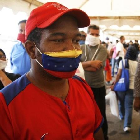 De máscara, homem aguarda para receber cesta básica fornecida pelo governo da Venezuela durante a pandemia - Humberto Matheus/NurPhoto via Getty Images