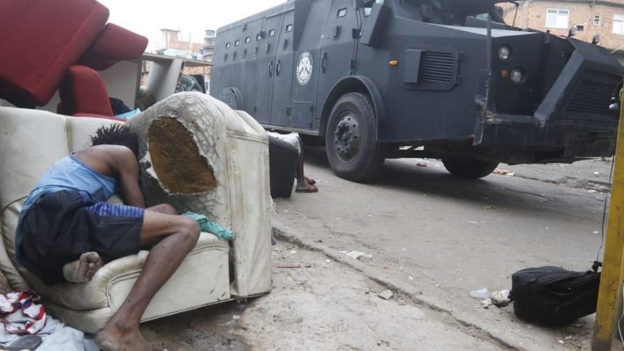 Pessoa aparentemente em situação de rua tenta se proteger de um caveirão durante a operação da Polícia Civil no Jacarezinho - REGINALDO PIMENTA/AGÊNCIA O DIA/ESTADÃO CONTEÚDO
