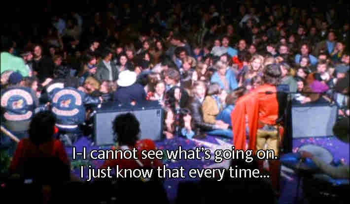 Visão do palco de Altamont: Mick Jagger veste uma capa de cetim preta e vermelha, pá direita, enquanto que um apreensivo Keith Richards tenta tocar, á esquerda. Note a proximidade perigosa do público em relação ao palco (FOTO: REPRODUÇÃO DE DVD)