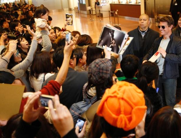 Tom Cruise (dir.) atende fãs ao desembarcar no aeroporto de Haneda, em Tóquio / Crédito: Issei Kato/Reuters