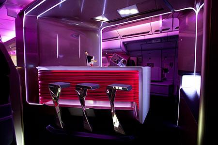 Passageiros da primeira classe podem tomar uma taça de vinho no bar do avião. Crédito: Reprodução/Virgin