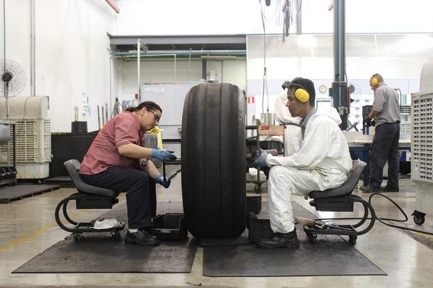 Funcionários da Latam desmontam a roda de um avião. Foto: Vinícius Casagrande/UOL