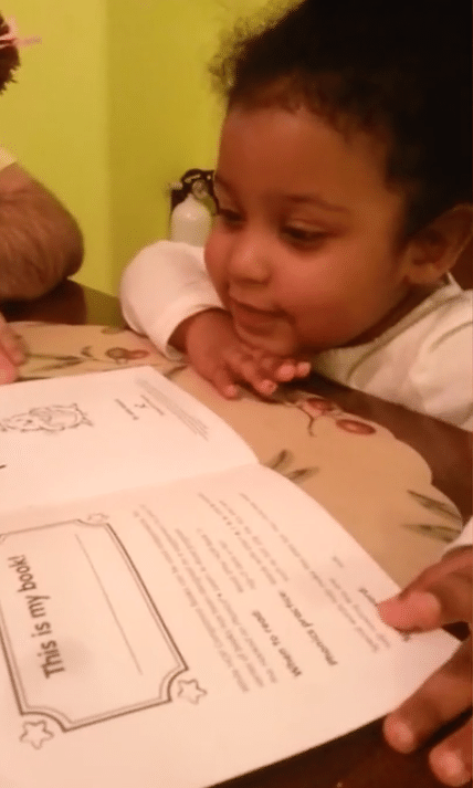 A garotinha lendo o primeiro livro.
