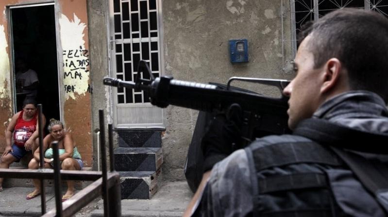 Policial anda pelas ruas e checa moradores para garantir a segurança durante uma operação no complexo de favelas da Maré no Rio de Janeiro (Ricardo Moraes/ Reuters)