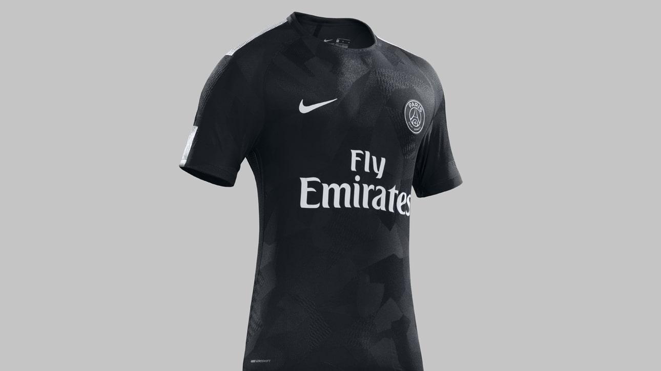 8908b2e981 A camisa tem o design camuflado em tons de preto e cinza bem escuro. Os  símbolos do PSG