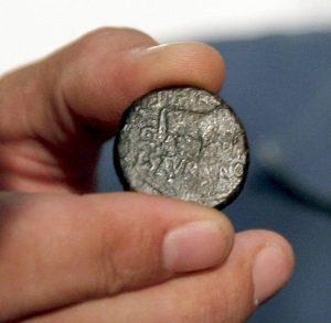 Arqueólogo exibe moeda de bronze romana antiga achada em escavação sob museu de Oviedo, na Espanha (imagem: J.L. Cereijido/EFE)
