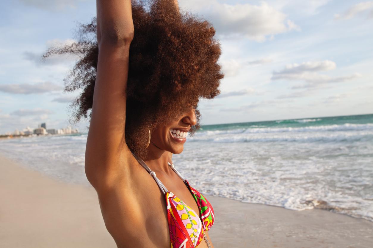 Mulher de cabelo crepso na praia