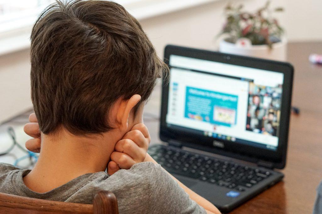 Criança olha para seu computador - Foto de Thomas Park no Unsplash