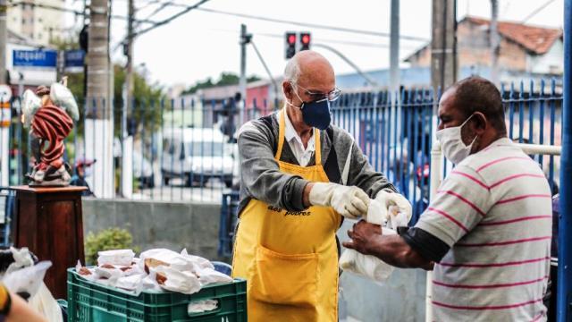 padre julio lancellotti entrega alimento a pessoa em situação de rua