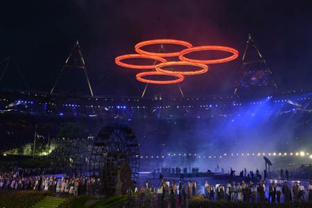 "Photo taken on July 27, 2012 shows freshly ""forged"" Olympic rings floating above artists performing during the opening ceremony of the London 2012 Olympic Games at the Olympic stadium in London. AFP PHOTO / GABRIEL BOUYS"