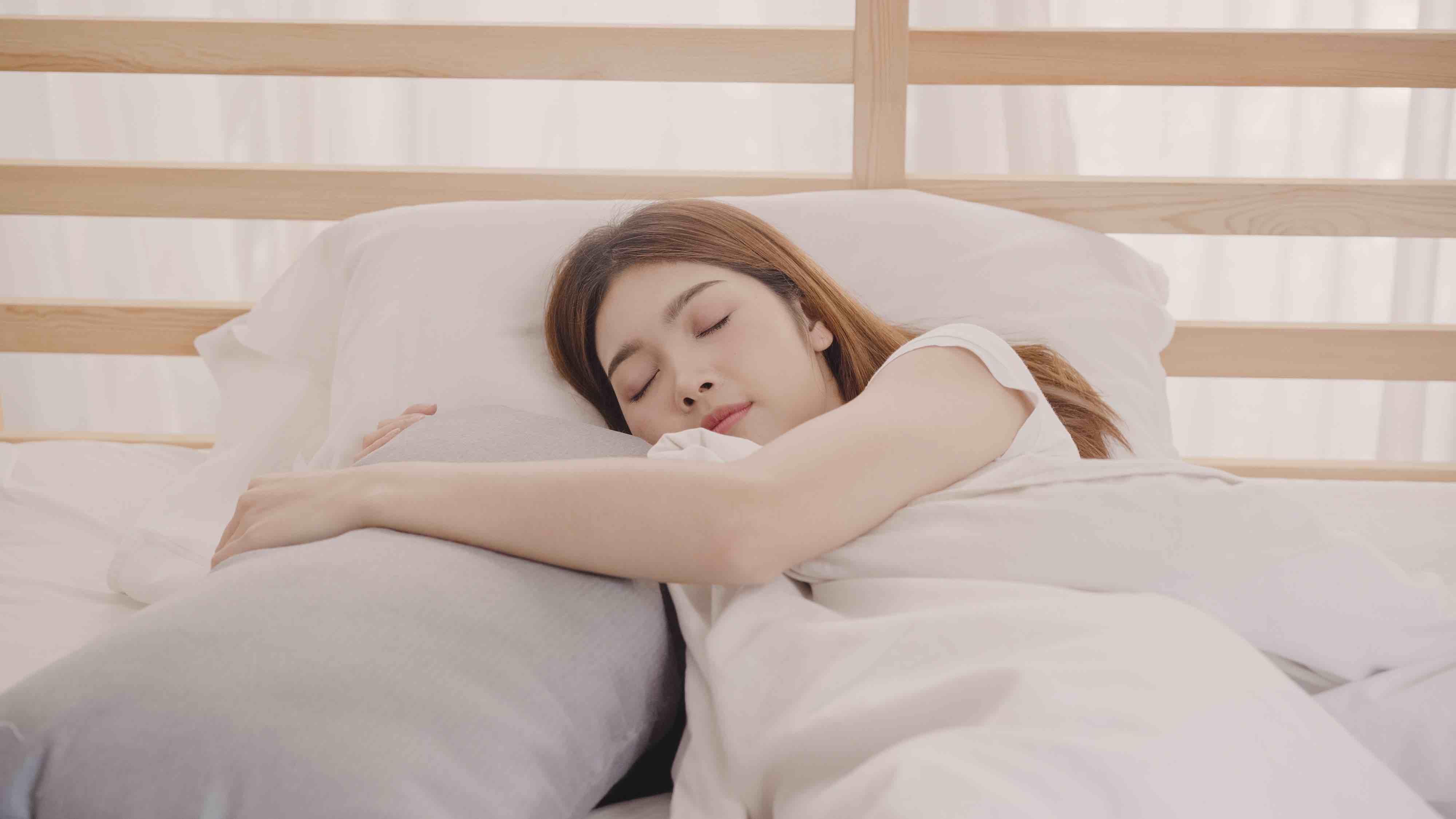Mulher dormindo agarrada emum travesseiro