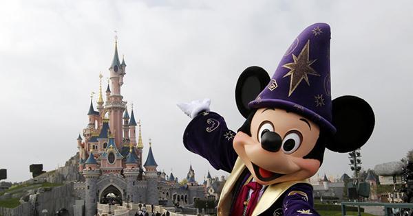 Mickey Mouse, personagem da Disney, posa em frente a castelo em parque temático na França