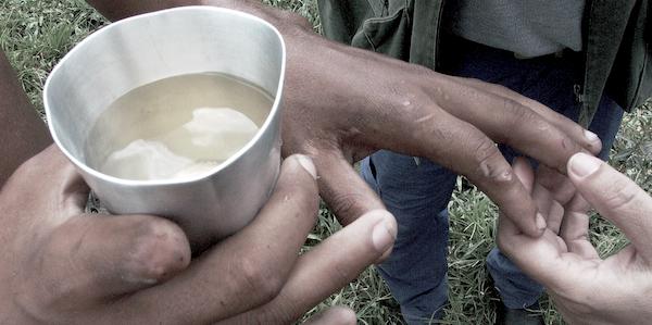 Trabalhador libertado mostra água que bebia, a mão machucada por falta de luvas na aplicação de pesticida e o dedo que perdeu na produção (arquivo pessoal)