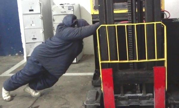 """Funcionário empurra bateria que pesava mais de uma tonelada. Segundo fiscal, a força necessária é descomunal. """"É só uma questão de tempo para ele se afastar"""". Foto: Divulgação MTE"""