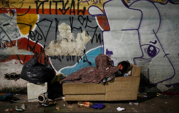 Pessoa em situação de rua usa sofá abandonado em noite de muito frio em São Paulo. Foto: Nacho Doce/Reuters