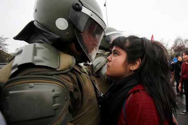 Menina encara policial no Chile em protesto no dia 11 de setembro, aniversário do golpe militar. Foto: Carlos Vera/Reuters