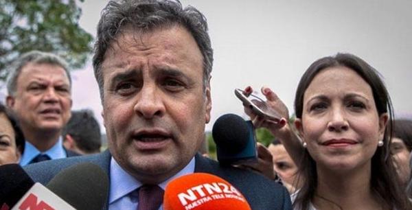 Aécio concede entrevista após confusão, observado pela deputada cassada Maria Corína e pelo senador Petecão ao fundo. Foto: El Mundo, de Caracas