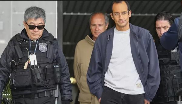 Odebrecht, de mãos no bolso, à frente de Alexandrino (já solto). O funcionário estava algemado. Foto: epoca.com